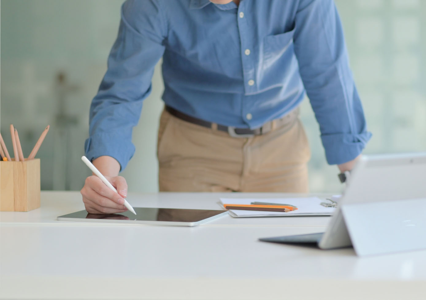 A man stands in front of desk, working with a digital pen on a tablet while reviewing work on a fold-out laptop.