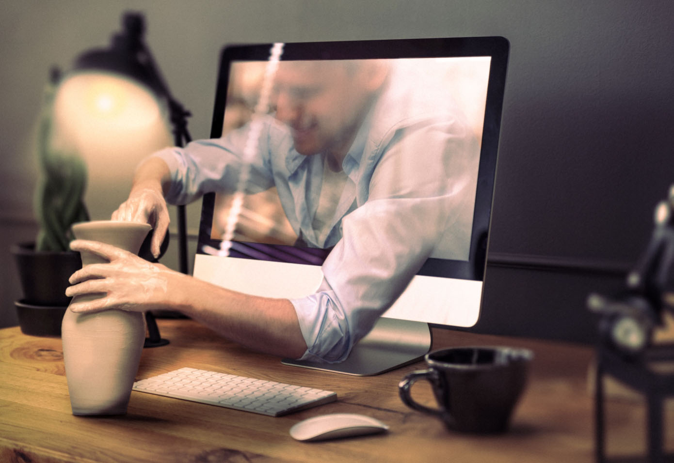 A digital man extends his arms out of a computer monitor's screen, which is sitting on a desk with a keyboard, mouse and mug, and is handcrafting a clay jar.