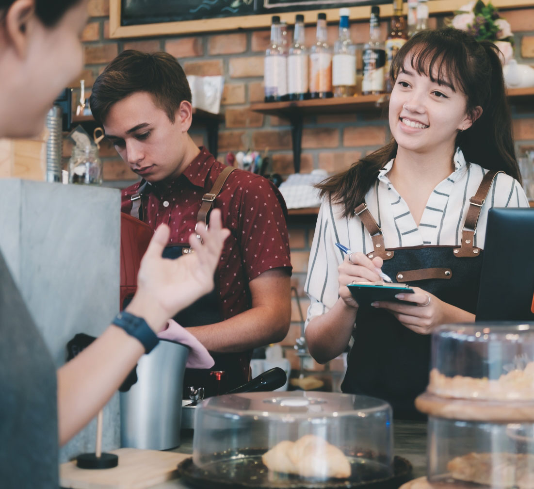 A young lady smiles while working behind the counter at a shop, listening and taking an order while conversing with a customer.