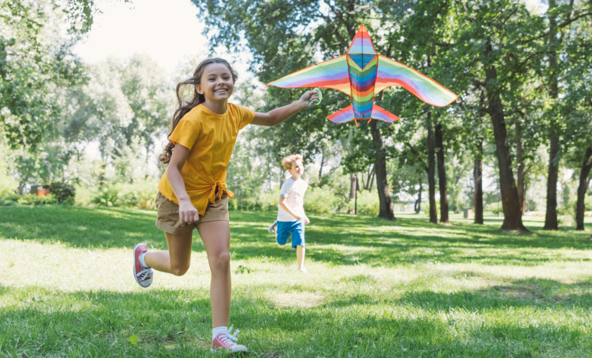 A young girl runs through a park while flying a rainbow-colored kite shaped like a bird and being chased by her younger brother.