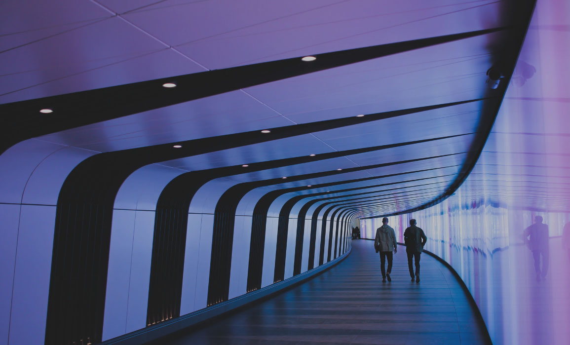 Two people walk down a curved hallway, which is tinted with a mauve color.