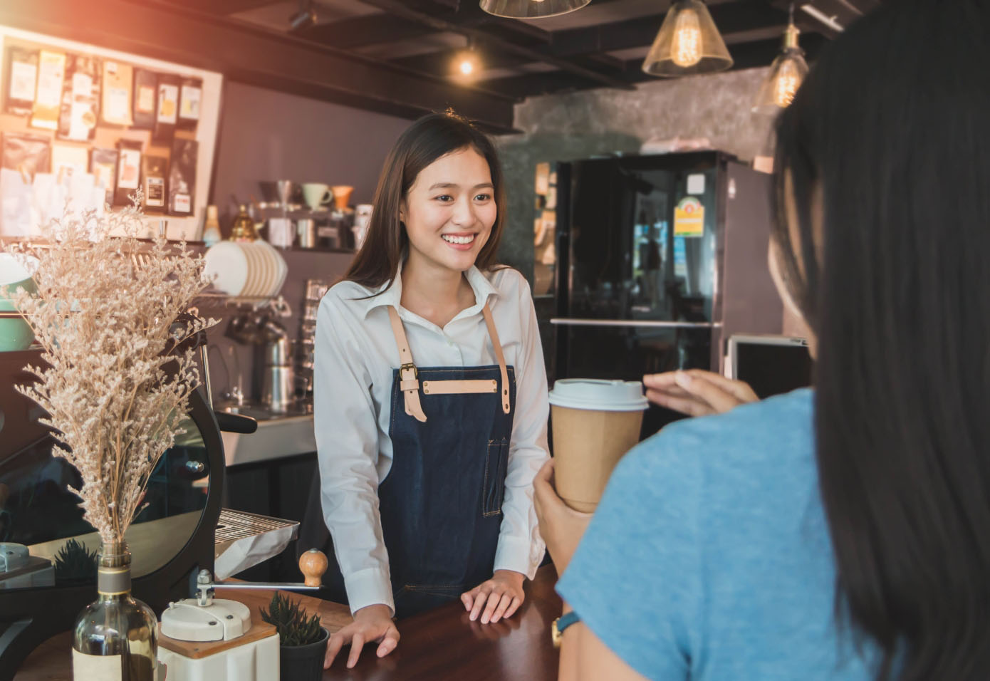 A barista smiling and conversing with a customer