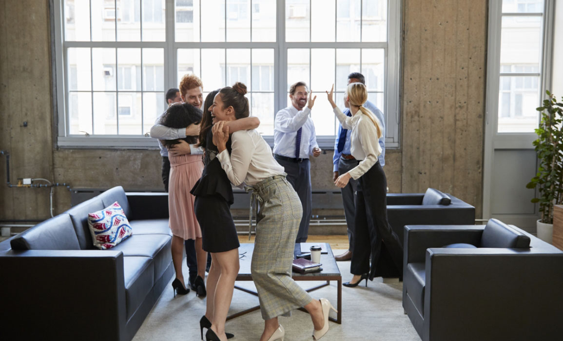 A group of professional men and women have stood up from their informal meeting, which took place on couches in a lobby, and are celebrating together. Some of the people are hugging, others high-five each other.